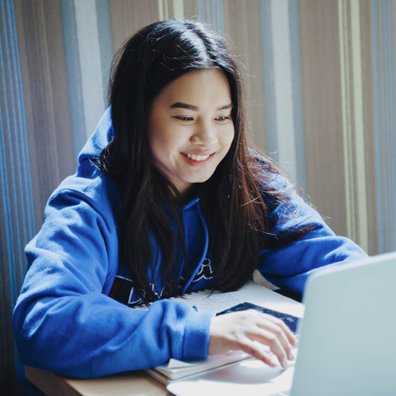 female student in blue hoodie sitting at a table with a laptop
