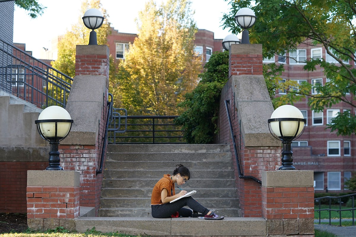 Young woman writes in notebook seated on steps on UMass Lowell campus