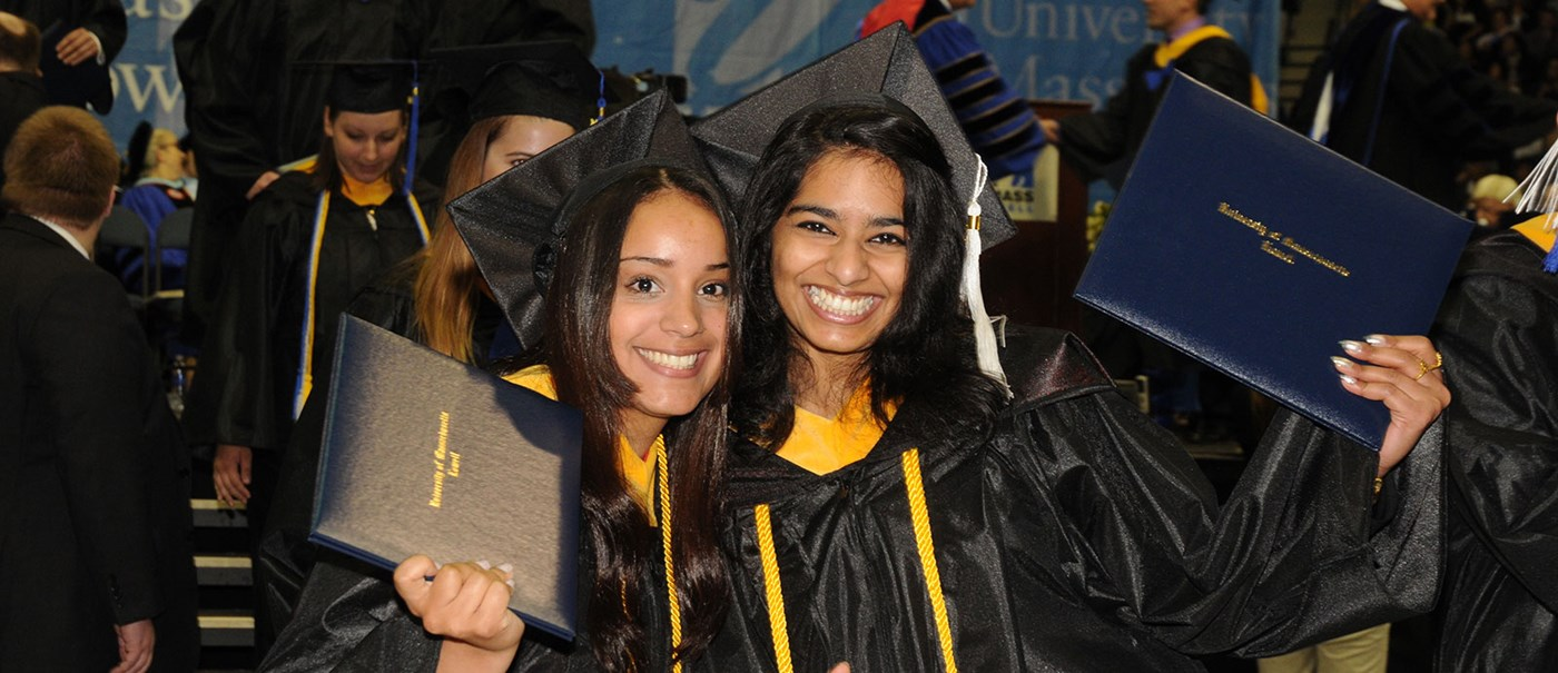 Two undergrad senior girls in their graduation cloth,  holding their degree .