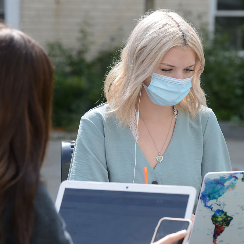 Young woman wearing mask works on laptop outdoors