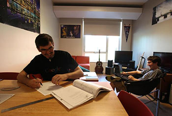 UMass Lowell sophomores, Alex Montemurro of Westford, and Connor Williams of Dennis, do homework in their dorm room. The school opened University Suites, a $54 million residence hall for 472 students that includes 88 four- and six-bed suites that feature living rooms and kitchenettes.