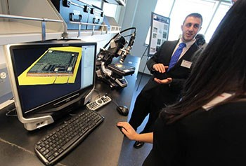 Kyle Homan, a doctoral student in electrical engineering, talked about printable electronics and nanotechnology at the opening of the Raytheon-University of Massachusetts Lowell Research Institute on Friday. Boston Globe photo by Mark Lorenz