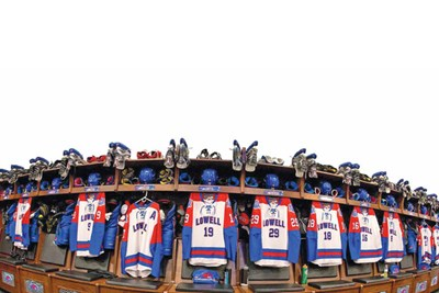 UMass Lowell hockey jerseys and skates hang in the River Hawks locker room