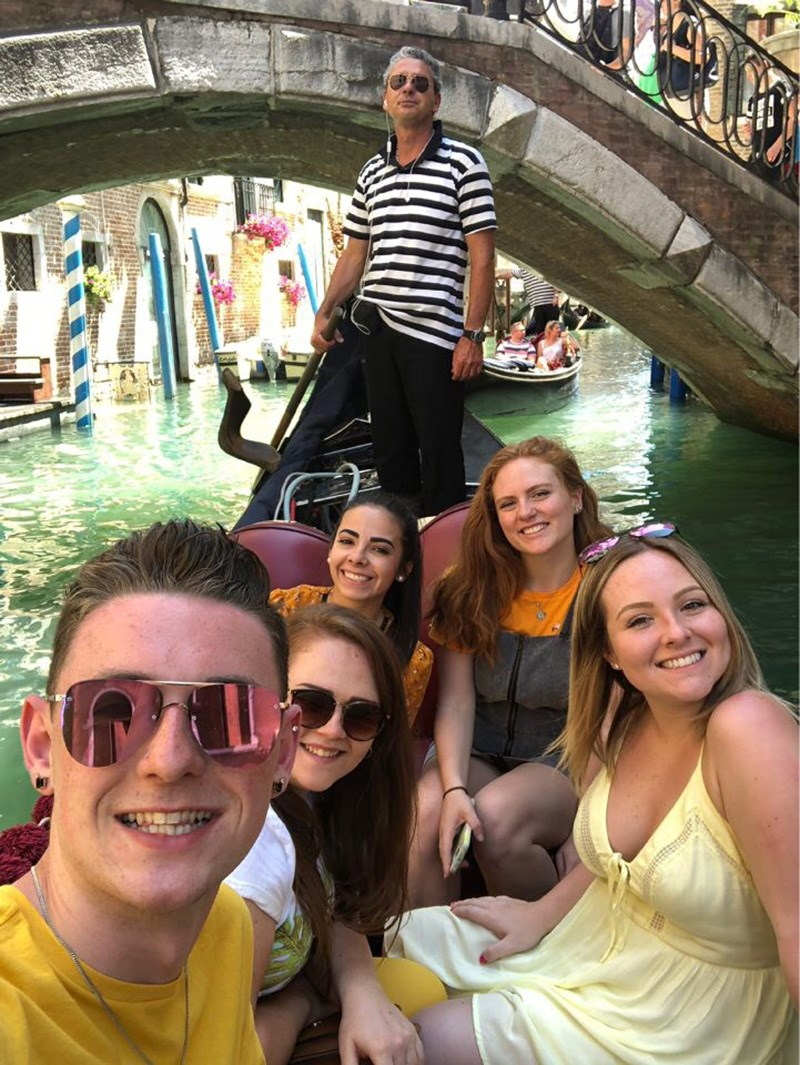 Group picture of UMass Lowell students on a gondola while explore Venice, Italy on a Study Abroad trip in the summer of 2018.
