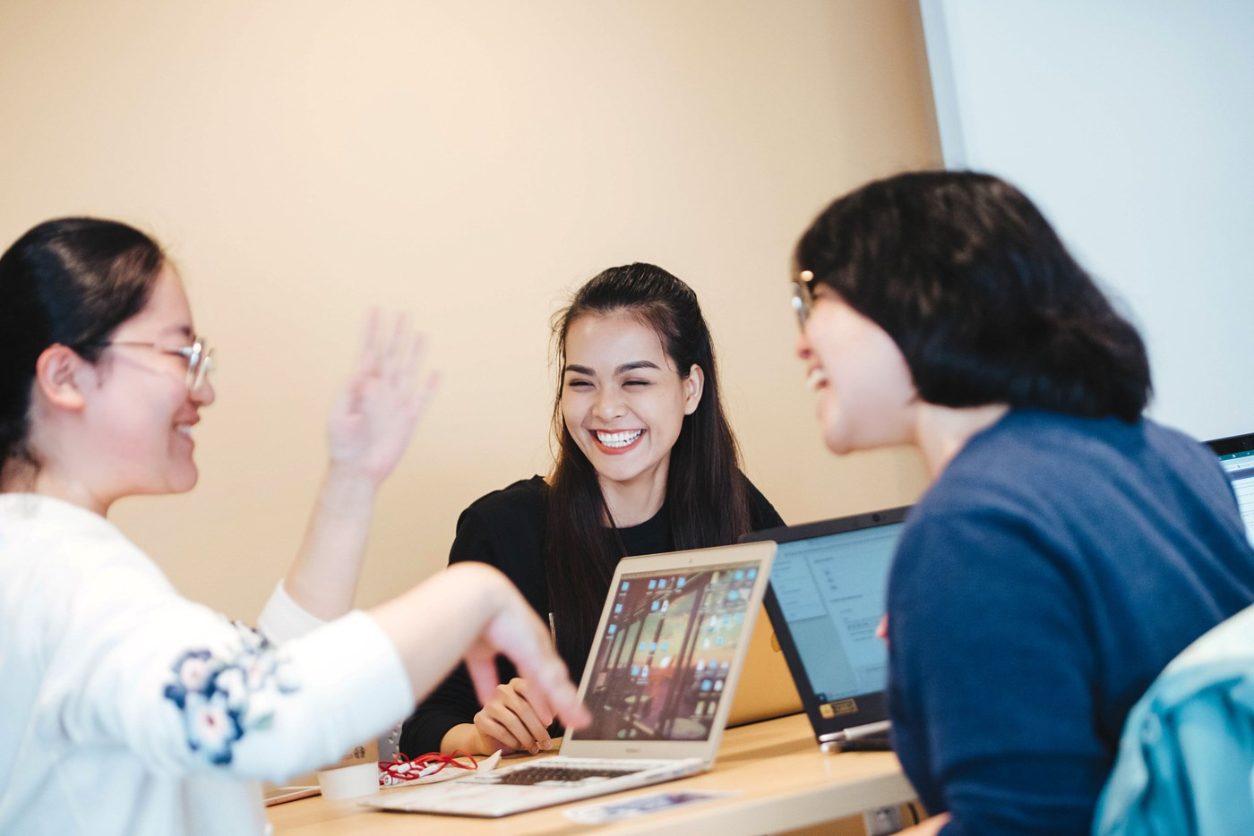 Three young Asian women laugh and smile while working at a table on laptops
