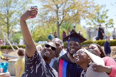 A UMass Lowell graduate takes a selfie outside the Tsongas Center with his family
