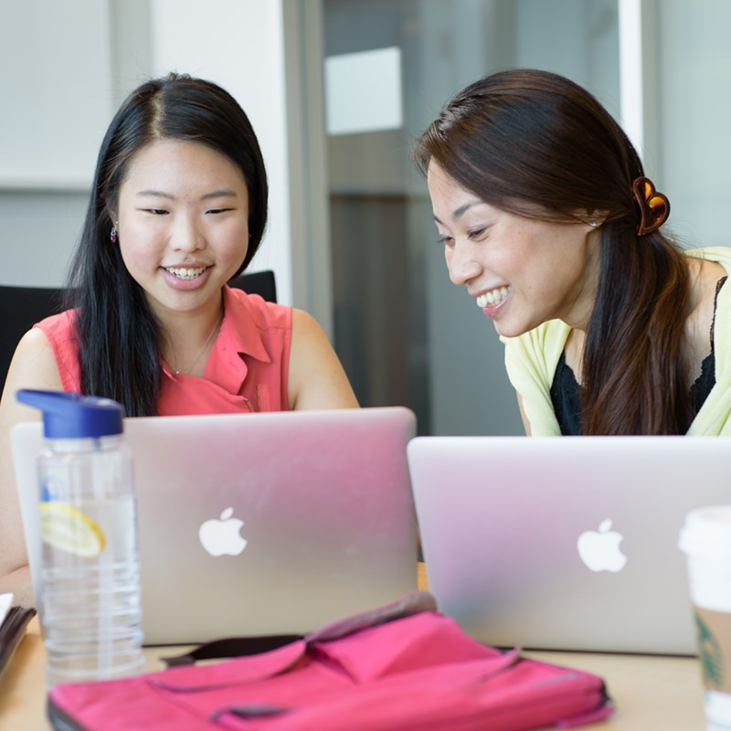 Two female grad students work on their laptops
