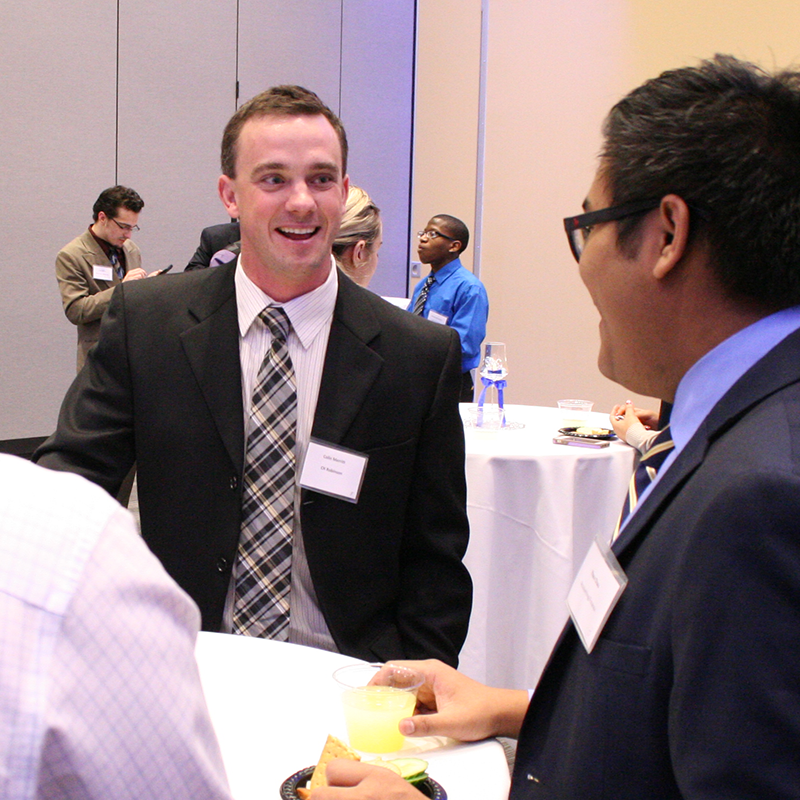 male students standing around a table networking