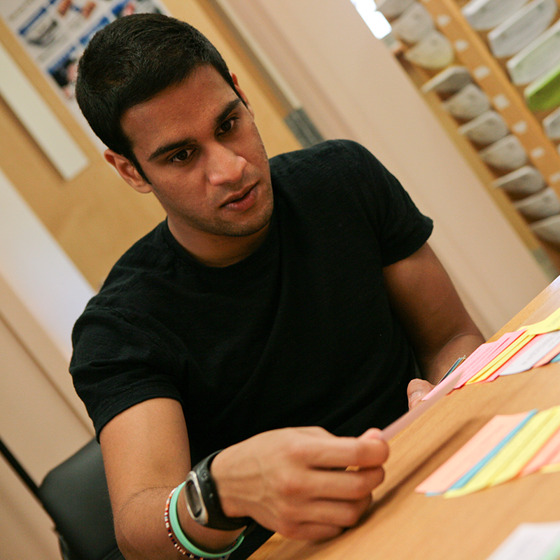 Grauduare student reviewing post-it notes