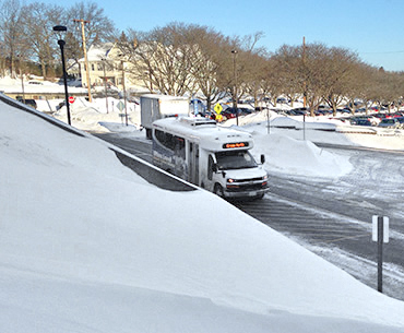 A green North Shuttle running during the winter in Umass Lowell.