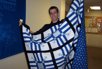 Graduate student Neil MacDonald displays the handmade quilt he won in a raffle sponsored by the GSE's Graduate Student Organization to raise money for the House of Hope family shelter.
