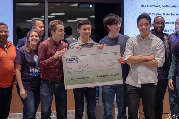 Flanked by event officials, the all-freshman winning team based at UMass Lowell, RAMS, collects the first-place prize money after literally putting in hard day's night at the 24-hour Haverhill Hackathon.