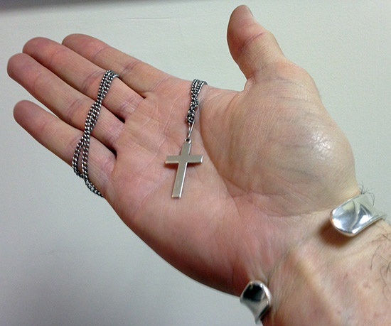 hand-holding-crucifix-cross-necklace