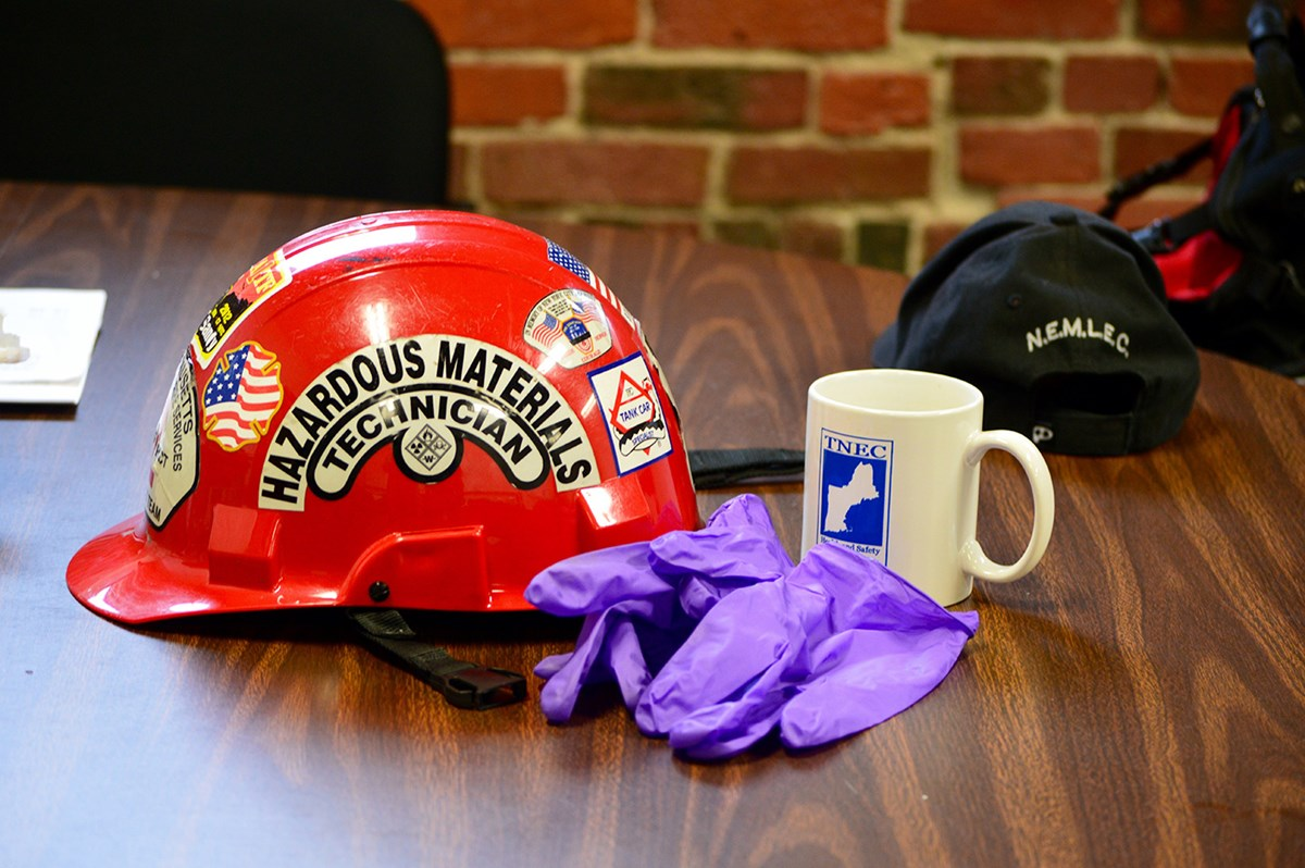 A hard hat sits on a table in the TNEC training center. The hard hat has a sticker noting that it is for hazardous materials technician. Next to the hard hat are a pair of plastic gloves and a coffee mug with the TNEC logo.