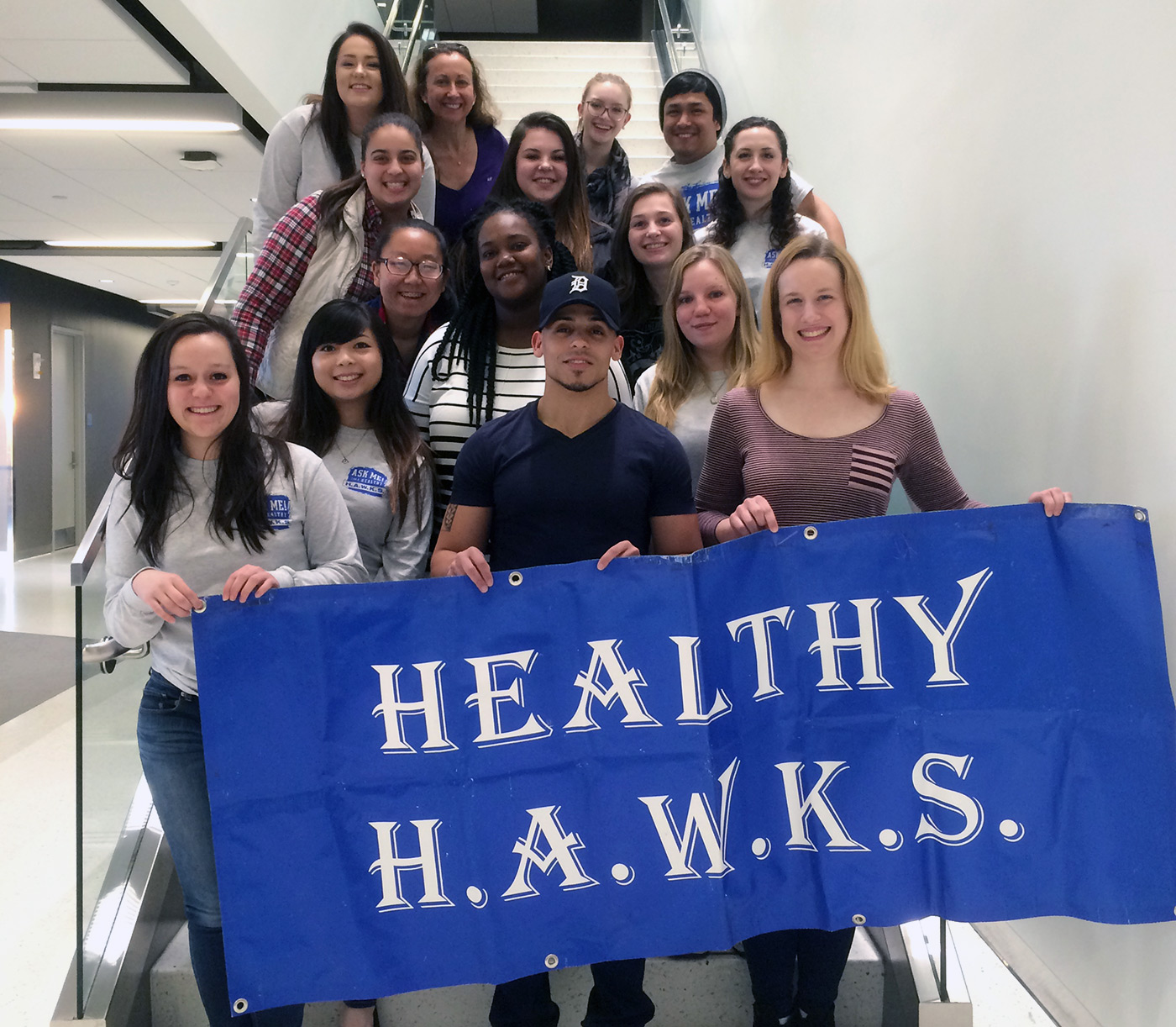 UMass Lowell Healthy HAWKS students pose for a group photo with a banner.