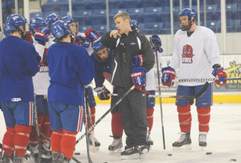 Coach Norm Bazin, center, runs through drills with the UMass Lowell hockey team at the Tsongas Center last Friday. Bazin, hired last spring, wasted no time turning the program around.