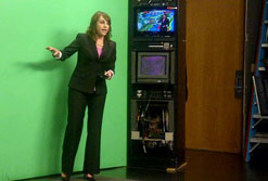 "UMass Lowell 2011 graduate Heather Jaffe works in front of the ""green screen"" while interning for NECN's meteorology department."