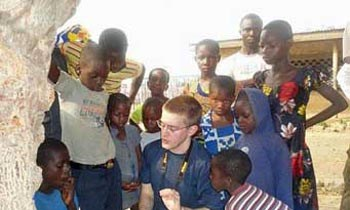 UMass Lowell student with children in Ghana
