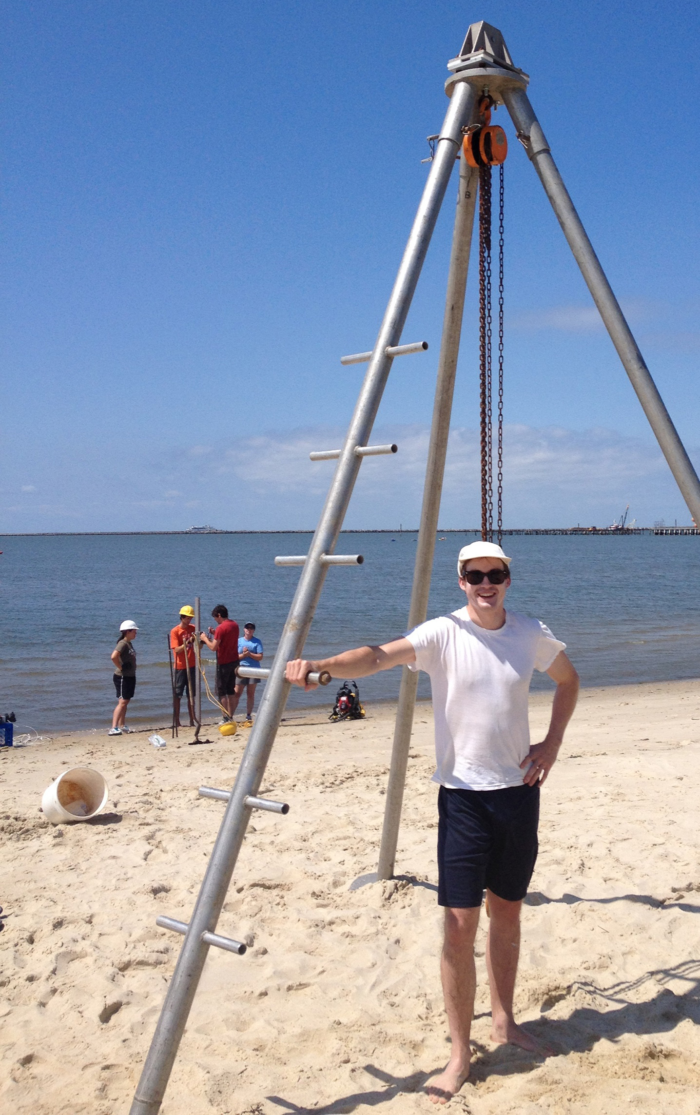 Assistant Professor James Heiss poses next to equipment at a beach. Heiss' research area is coastal groundwater dynamics and nutrient cycling in nearshore aquifers. I am interested in the influence of land-sea processes (tides, sea level rise, terrestrial recharge) on the exchange of water and chemicals between groundwater and surface water in estuarine, beach, bay, marsh, and marine environments. This work has direct implications for groundwater resources and water quality of coastal systems.