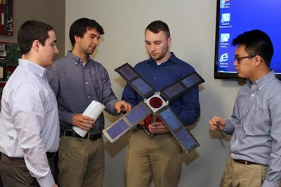 UMass Lowell students Charles Barbon, Jacob Hulme, William Mann and Dat Le are building a satellite that space agency NASA hopes to launch in 2018.