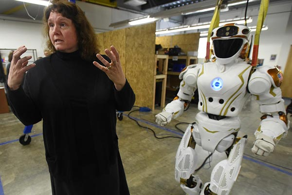 QUITE A RIDE: NERVE Center Director Holly Yanco, above, works at University of Massachusetts Lowell with Val — short for Valkyrie — to improve the robot's communication skills.