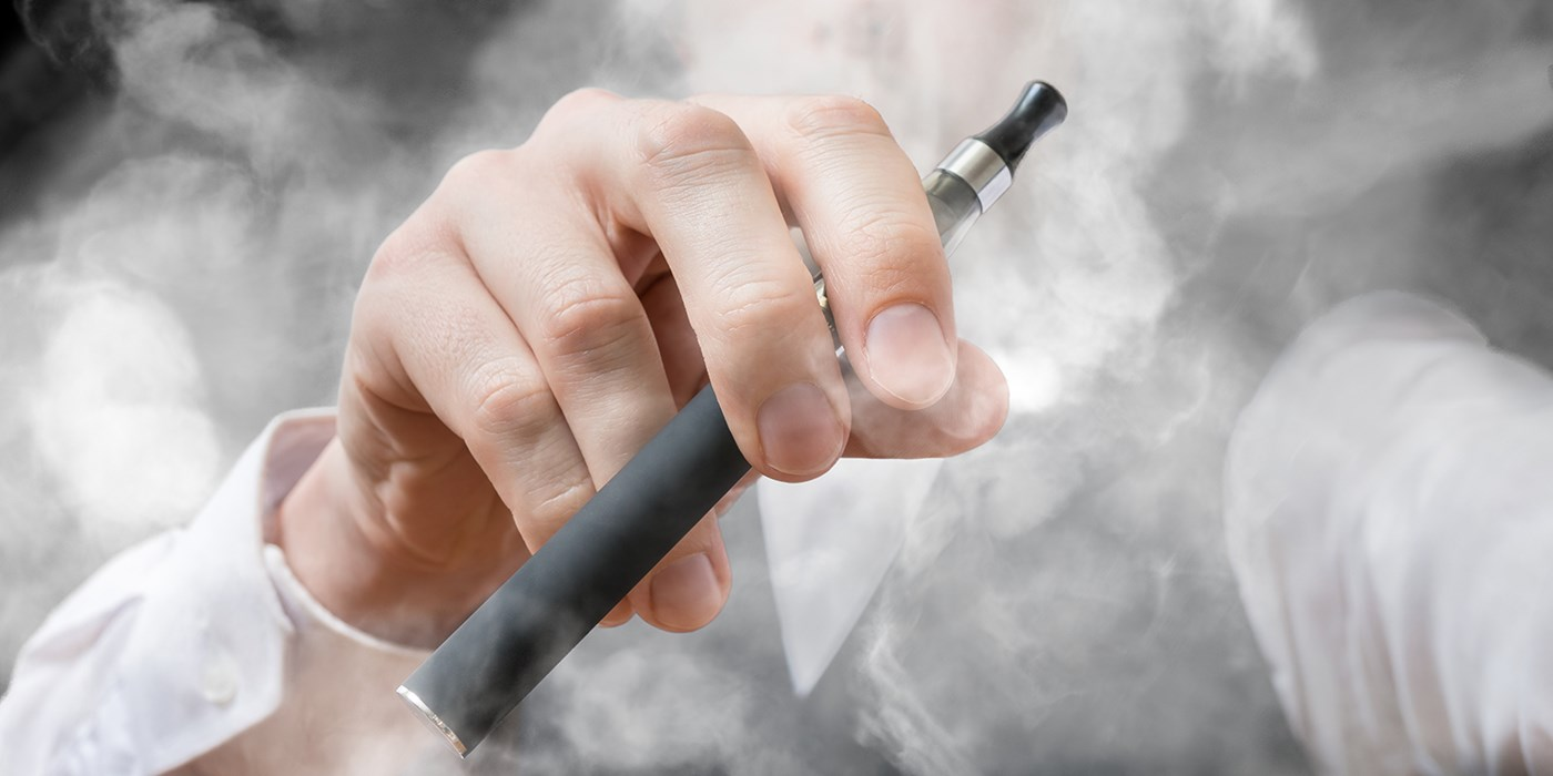 Hand holding vaping e-cigarette surrounded by smoke