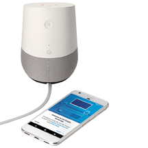 Google Home device pictured alongside with a smartphone displaying the Google Home app