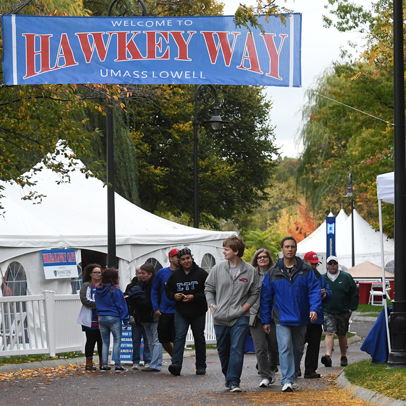 Students walking under Hawkey Way sign