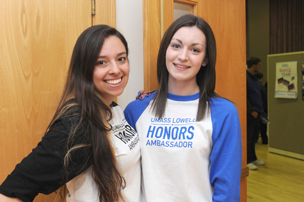 Two female honors ambassadors smile wearing matching baseball t-shirts during a welcome day event