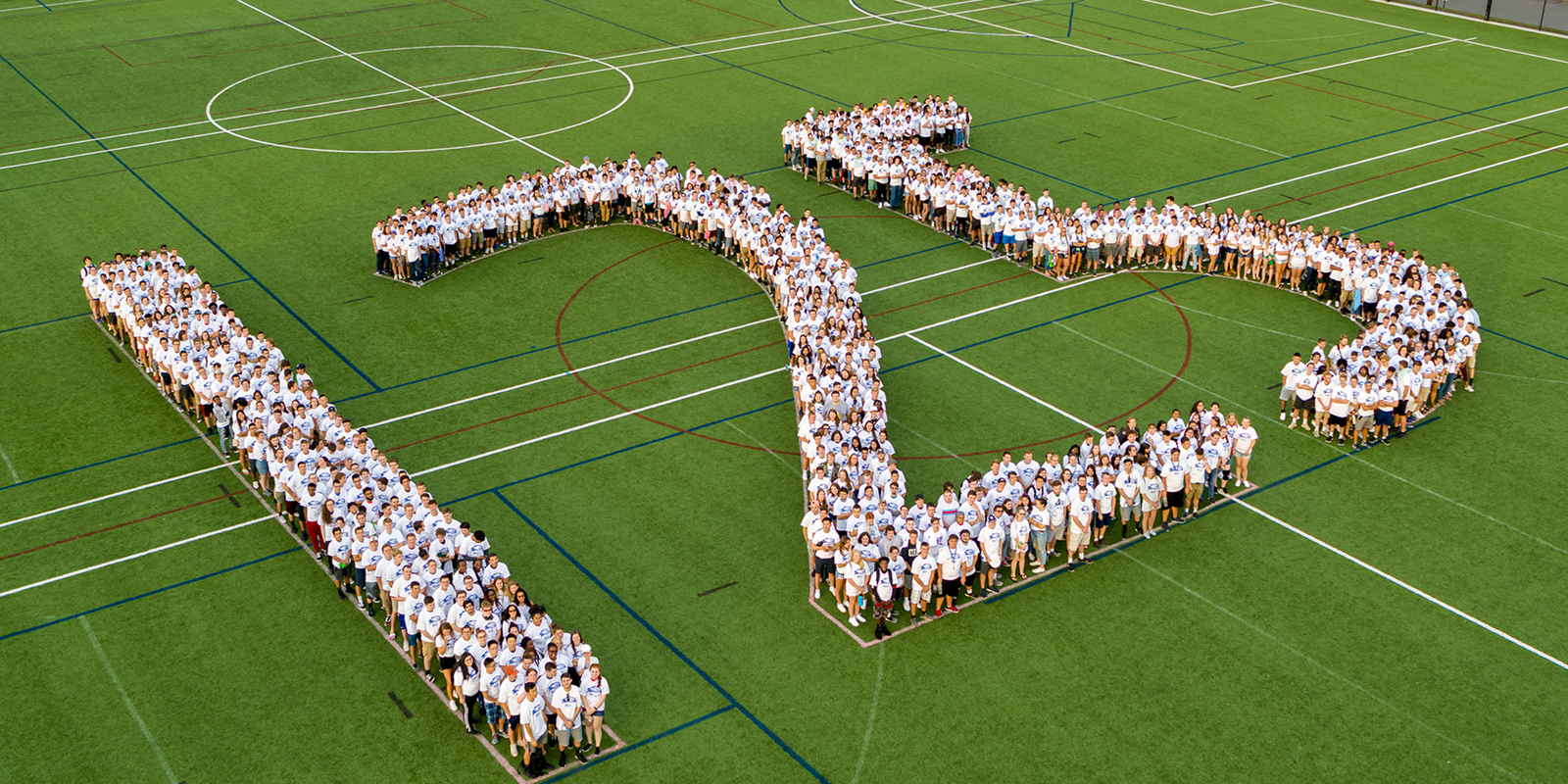 Students stand in white UML t-shirts within a human 125 on the green Campus Rec Complex field