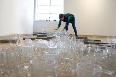 Evelyn Rydz arranges thrifted glassware into a symbolic Merrimack River for her part of the current Local Ecologies exhibit in Moloney Gallery.