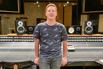 Luke Bilodeau standing in front of a sound board in a recording studio