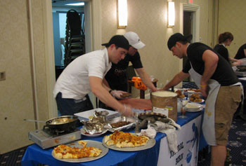 Graduate students Thomas Sniezek, Timothy Duffy and Jason Skeldon put the finishing touches on their winning meal in the third annual campus Iron Chef competition.
