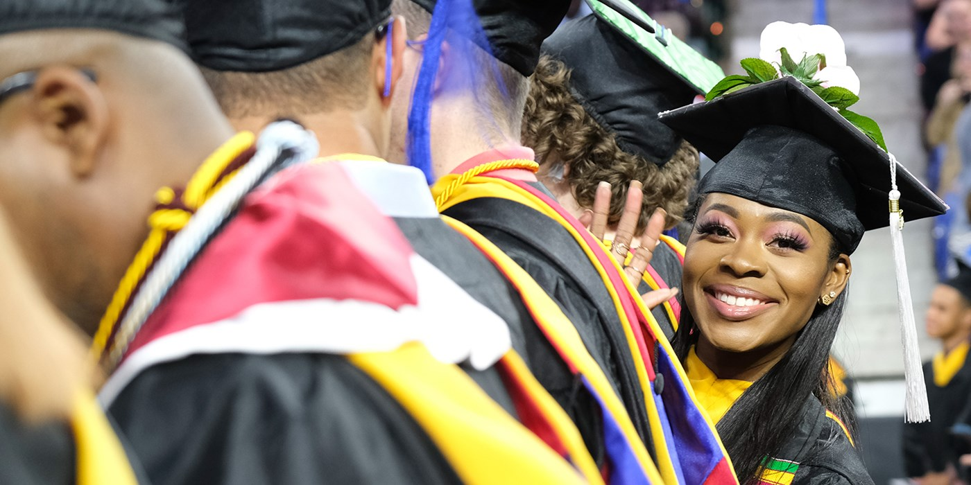 Smiling young black woman in graduation garb waves to camera