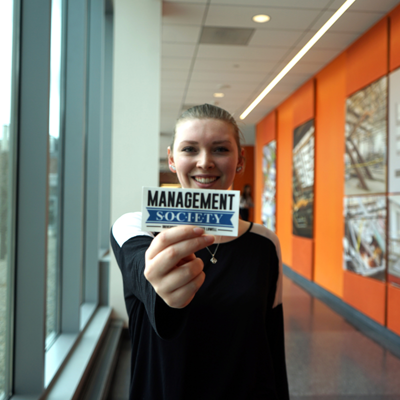 Kelly Bradford holds a Management Society sticker in the Pulichino Tong Business Center