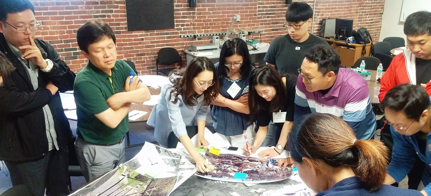 Students from Korea attend a chemical safety training presented by the Toxic Use Reduction Institute (TURI) at UMass Lowell's TNEC training center. The students are pictured viewing photograph's of various chemical disaster spills.