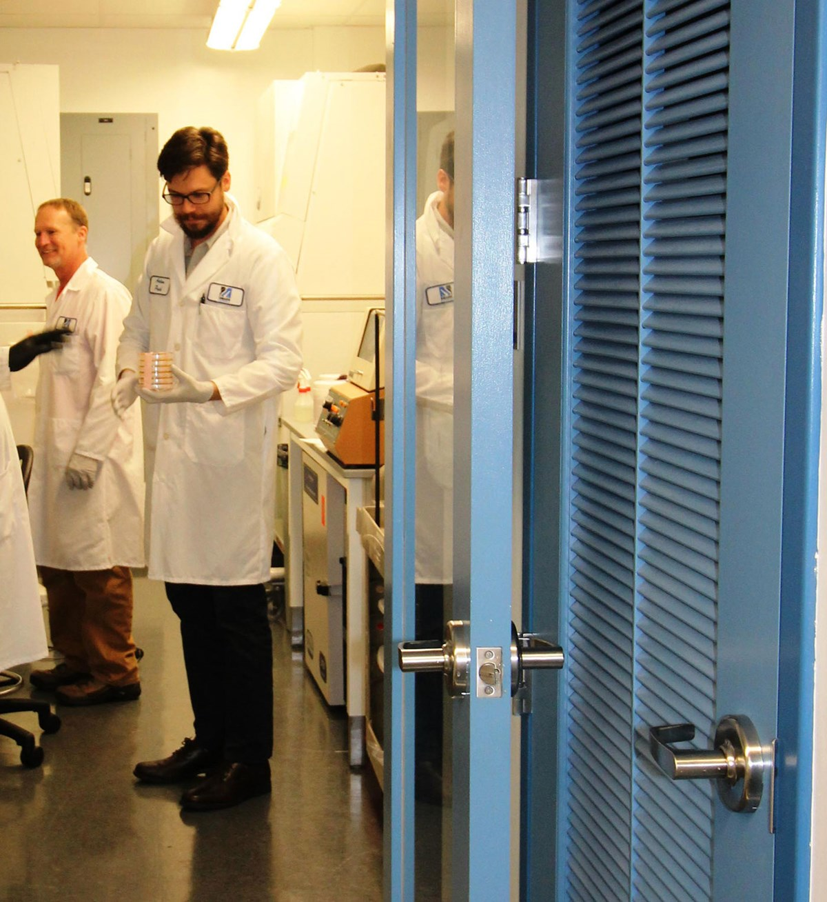 Dorrs opening into a lab with men working