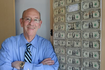 Larry Siegel poses with a collection of three neat columns of dollar bills, $5 bills and a couple of higher denominations—in all, 41 bills totaling $134— mounted on the back of a cabinet door