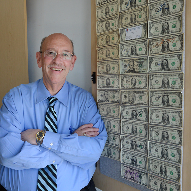 Larry Siegel stands in front of a bulletin board covered in $1 bills
