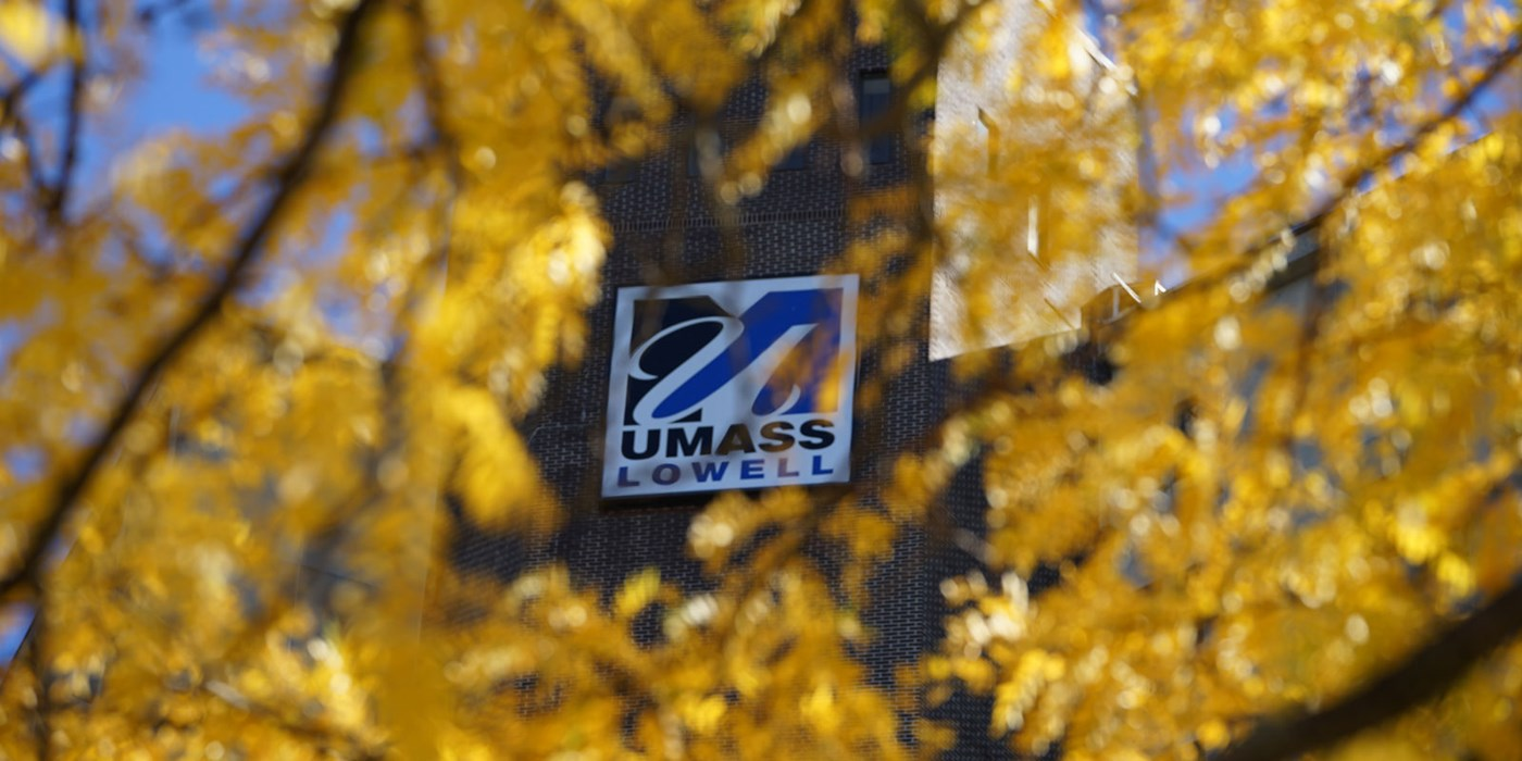 UMass Lowell logo on building seen through yellow tree leaves