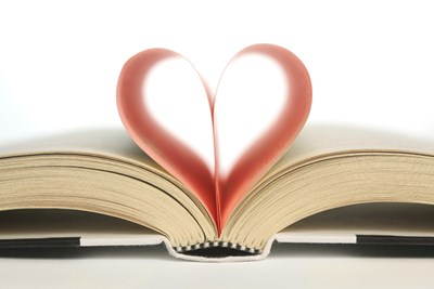 An open book with two pages folded inward to form a heart shape