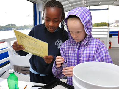 Lowell fourth graders examine water samples on boat