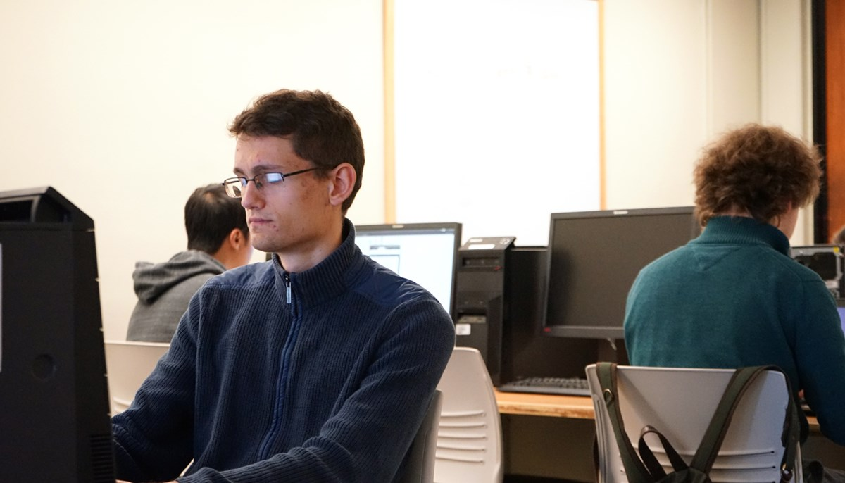 Lukas Lazarek works on a computer in a lab