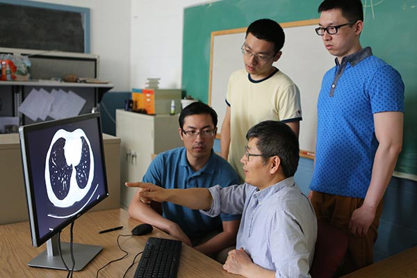 Assoc. Prof. Hengyong Yu, seated in front, discusses the project with his team, from left: postdoctoral researcher Yanbo Zhang, electrical engineering Ph.D. student Miaoshi Wang and biomedical engineering Ph.D. student Rui Liu—at Yu's Imaging and Informatics Lab in Ball Hall on North Campus.
