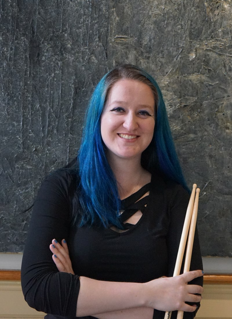 headshot of Maddie May Scott holding drum sticks