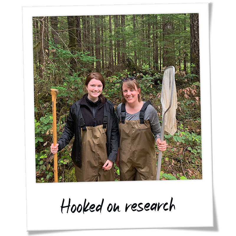 """Polaroid"" photo of Maeve Moynihan working with Asst. Prof. Natalie Steinel wearing fishing gear and holding nets - handwriting on photo frame reads ""Hooked on research"""