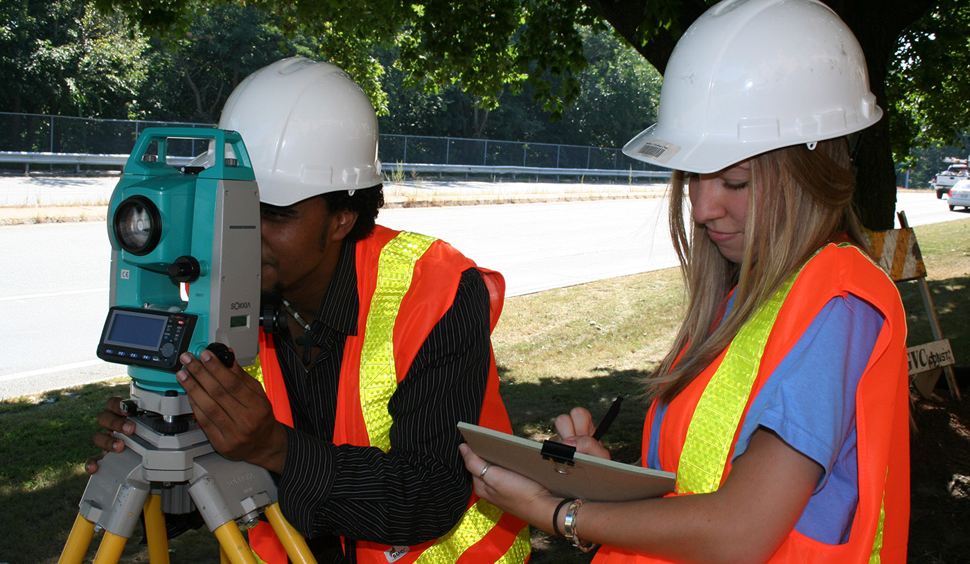 A male and female UMass Lowell student both wearing hard hats and surveying.