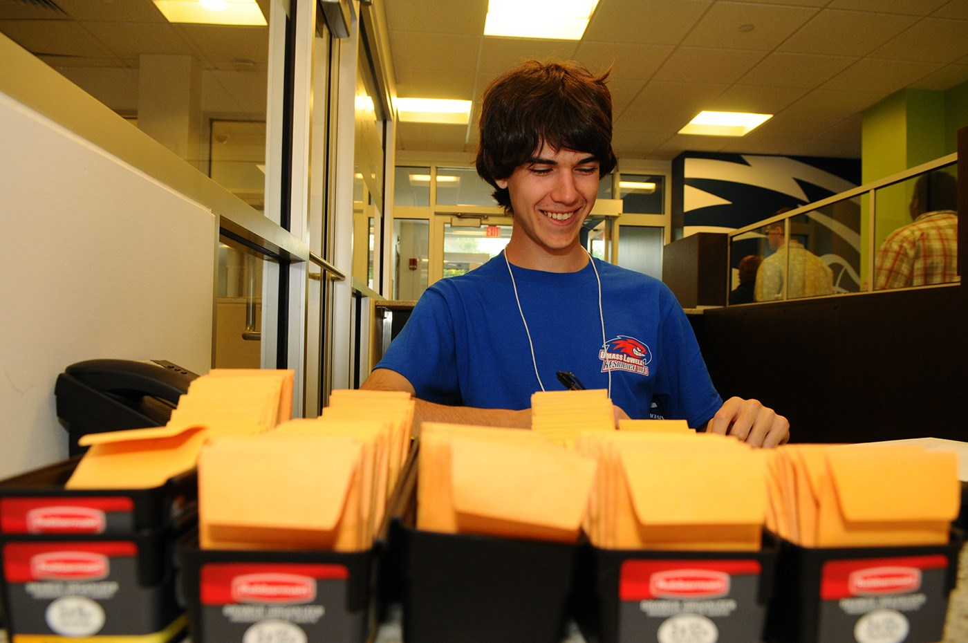 A male reslife student sorting envelopes.