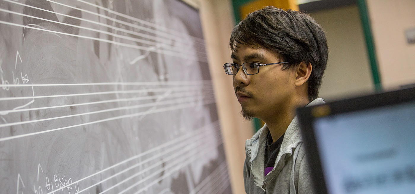 A male student writing music/composing on a chalk board.