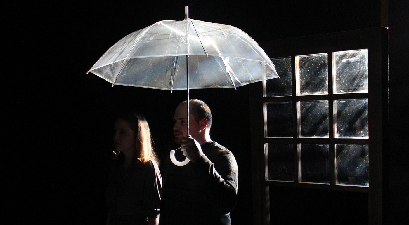 A male student holding an umbrella on stage next a female student with an window behind them in the dark during a UMass Lowell Theatre Arts production.